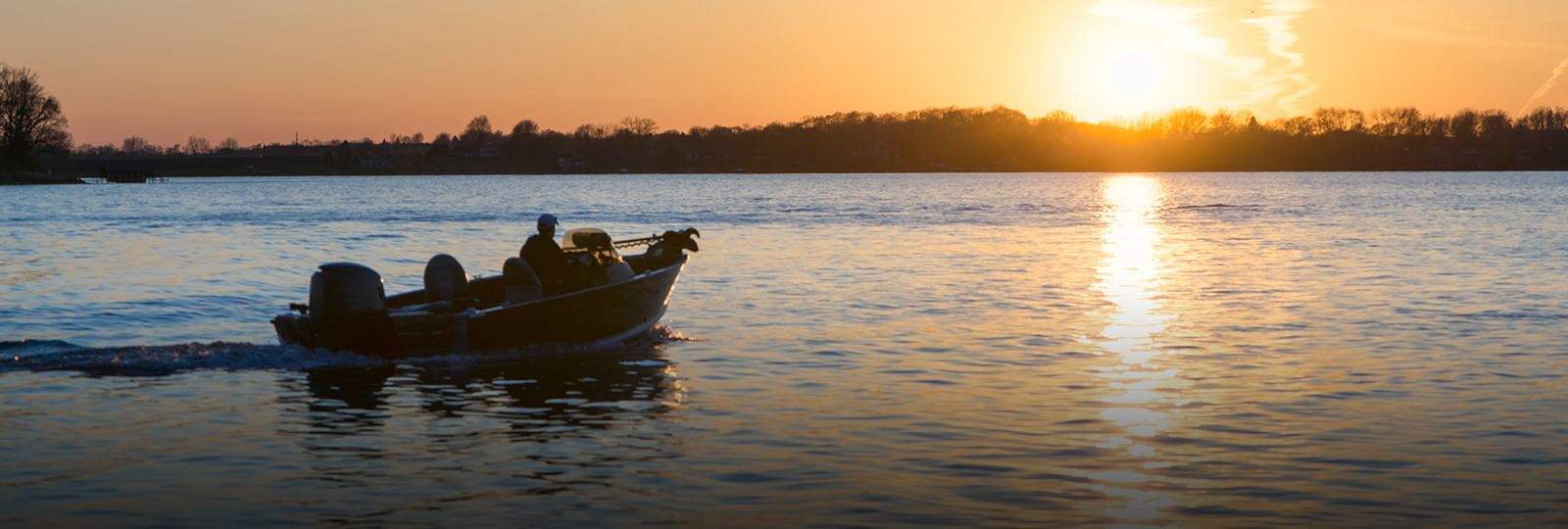 photo of man boating at sunset