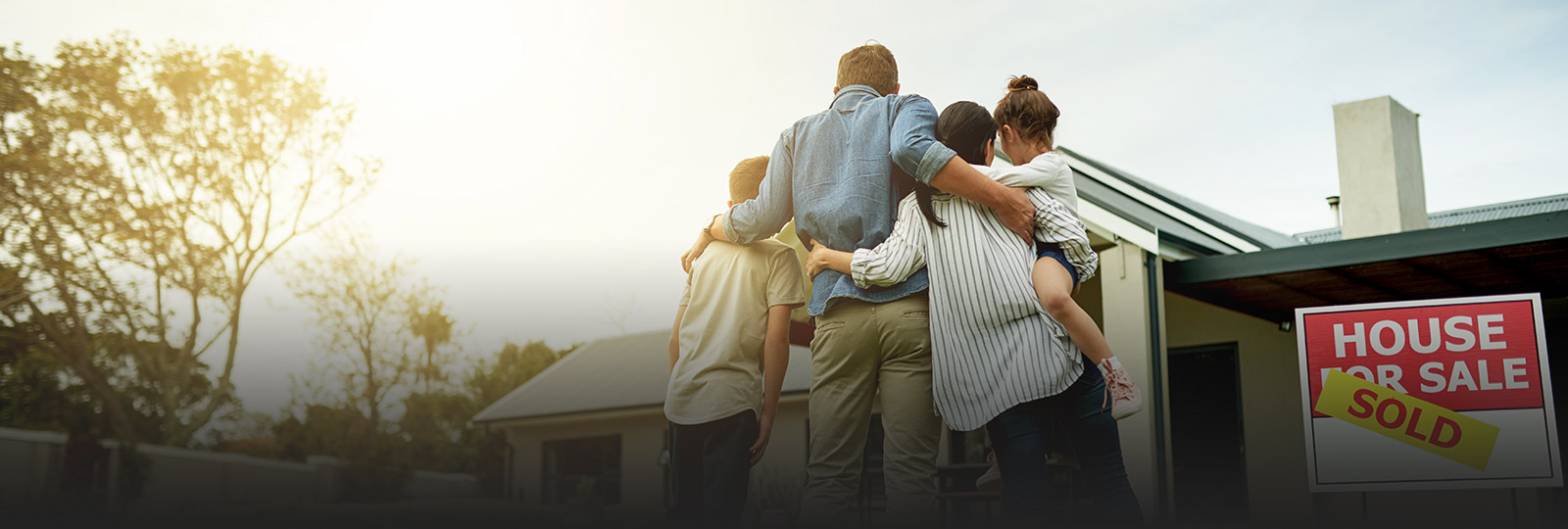 family with arms around each other looking at a sold house