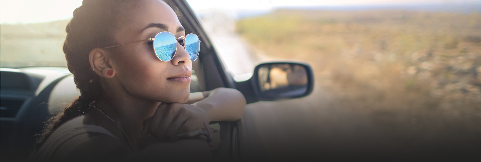 woman wearing sunglasses looking out a car window